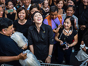 11 NOVEMBER 2016 - BANGKOK, THAILAND: YINGLUCK SHINAWATRA laughs at a joke a supporter told her at a rice distribution sale in the Bangkok suburbs. Yingluck Shinawatra, the former Thai Prime Minister deposed in a coup in 2014, has started selling rice directly to Thai consumers. She buys the rice from farmers at market prices and then sells it to urban consumers at the price she paid. She said she's doing it to help out farmers, who are trying to deal with depressed prices. Yingluck is facing prosecution on corruption related charges going back to a rice price support scheme her government used to try to help farmers in 2011 and 2012. Even after the coup, she is still personally popular and hundreds of people showed up to see her at the rice distribution point at a mall in Samut Prakan province, in suburban Bangkok.   PHOTO BY JACK KURTZ