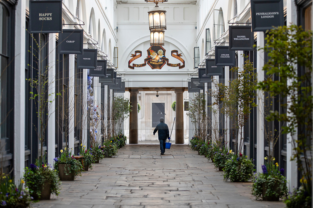© Licensed to London News Pictures. 19/03/2020. London, UK. A man carries a mop and bucket through an empty row. of shops in Covent Garden as the Coronovirus outbreak escalates in London. The government has announced a series of measures designed to slow the spread of the virus, which is now spreading more rapidly in the capital than in other parts of the country. Photo credit: Rob Pinney/LNP