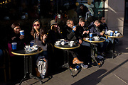 Afternoon coffee drinkers sit outside Caffe Nero in Old Brompton Street in Soho. Blue cups from this UK coffee cafe brand are seen in spring sunshine - a scene of al fresco London cafe society in the heart of the capital's bohemian, media and film industry. Gerry Ford founded Caffè Nero in 1997 and today, Caffè Nero has over 500 stores globally with more than 4,000 employees.