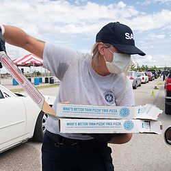 Austin, TX USA August 26, 2020: Austin fire official Megan Tarpey help east Texans and west Louisiana residents get settled with pizza at the Circuit of the Americas race track after evacuating low-lying areas about to get hit by Hurricane Laura on the Gulf Coast. Laura is expected to make landfall overnight as a Category 4 storm and wreak havoc along the Texas coast and inland.