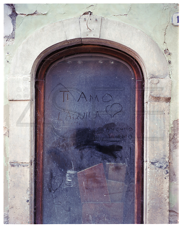 "A sentence on a shop window: ""I love you L'Aquila"" and under, a reply : ""I love you too""."