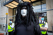 Police keep a close eye on Oil Slick, black rebels demonstrate as part of the Extinction Rebellion 'Shell Out' protest on 8th September 2020 in London, United Kingdom. The environmental group gathered outside the Shell building to protest at the ongoing extraction of fossil fuels and the resulting environmental record. Extinction Rebellion is a climate change group started in 2018 and has gained a huge following of people committed to peaceful protests. These protests are highlighting that the government is not doing enough to avoid catastrophic climate change and to demand the government take radical action to save the planet. (photo by Andrew Aitchison / In Pictures via Getty Images)