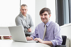 Businessmen using laptop in office, smiling