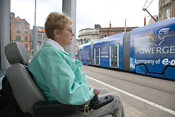 Woman wheelchair user waiting by a shelter at the  tram stop,
