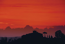 Europe, Italy, Tuscany, silhouette of villa and trees at sunset