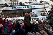 Conduit Street off Regent Street. UK Uncut flashmob occupy Starbucks to draw attention to the fact that they have paid no corporation tax for the last three years, and that the tax that rich companies haven't paid, would pay for the cuts the government is making to public services.