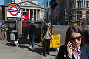Surrounded by other Londoners, an elderly lady shields her face outside one entrance of Bank Underground Station in the City of London, the capitals ancient, financial district, on 14th May, in London, England.