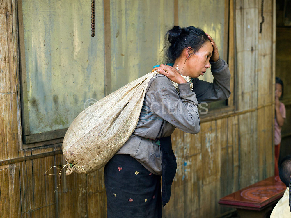 A Hmong ethnic minority woman in Ban Long Lan carries a sack of Arabica coffee cherries harvested for 'Saffron coffee', Luang Prabang province, Lao PDR. The coffee is grown in the high mountain peaks and plateaus in Luang Prabang over 800 meters above sea level. In November, December and January Saffron Coffee coffee farmers gather all of their family members to hand pick only the red-ripe cherries. It will take several passes over these few months to harvest all of them. These farmers were once producers of opium, but who have been impoverished by lack of a replacement crop in the wake of opium's prohibition by the Lao government. Saffron Coffee's goal in helping these farmers grow coffee is to give them a viable and sustainable cash crop, developing their economy, and thus giving them the ability to buy medicines and send their children to school.