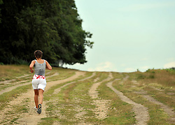 © licensed to London News Pictures. RICHMOND, UK.  02/08/11. A jogger runs through dry land at Richmond park. People and animals in the hot sun today (2nd August 2011) in Richmond Park, Surrey. Temperatures are set to reach 30 degrees Celsius in some parts of London over the next few days.  Mandatory Credit Stephen Simpson/LNP