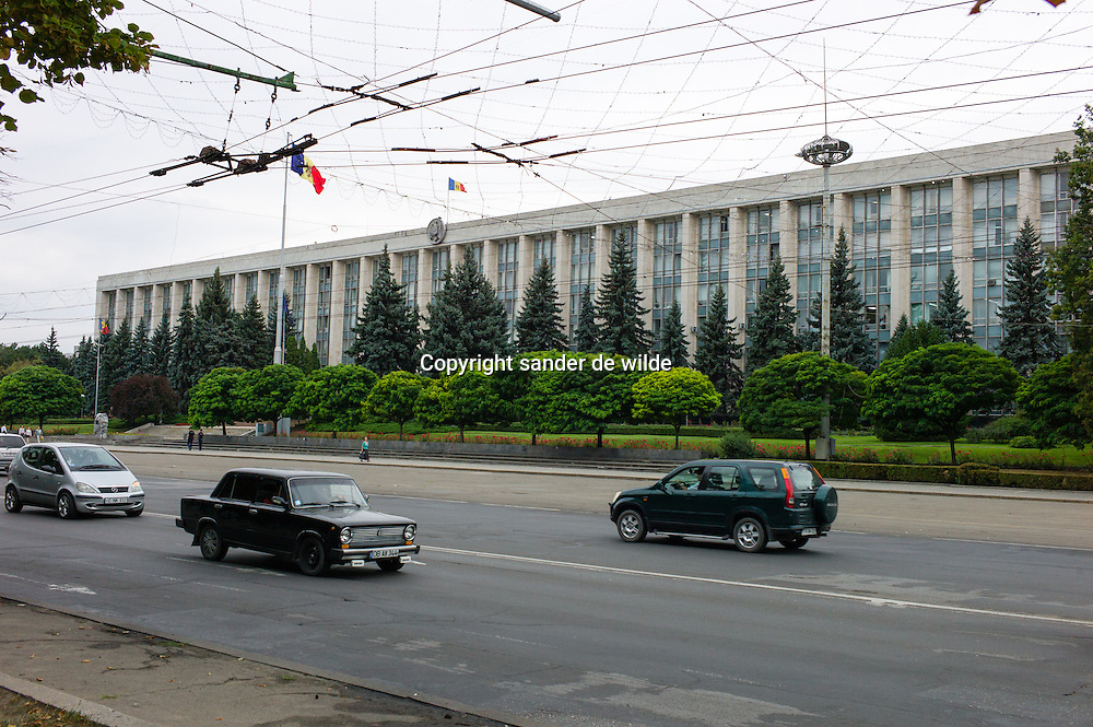 An typical soviet style building  in Chisinau, Moldova with lada car passing by in the city center traffic axe