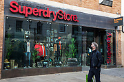 "A man wearing a face covering walks past a branch of fashion chain Superdry on the second day of England's second coronavirus lockdown on 6 November 2020 in Windsor, United Kingdom. Only retailers selling ""essential"" goods and services are permitted to remain open to the public during the second lockdown but Superdry has reported a 52% increase in online sales in 2020."