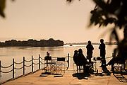 Tourists on jetty at sunrise by lower Zambezi River in Mana Pools National Park, Zambia