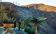 12062017 - Bel-Air, California USA:  Members of the Los Angeles Police Department gaze at damage along Casiano and Linda Flora Road during the Skirball Fire in Bel-Air area of Los Angeles, California. The fire, which started early Wednesday morning has burned 150 acres, destroyed 6 homes, and is 5-percent contained. Firefighters are staying in the area overnight where embers are still burning, and Santa Ana winds are expected to spread the fire. Hundreds of residents have been evacuated. (Photo by Jeremy Hogan) ©2017 All rights reserved