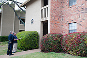 (L to R) Alan Bull and Raul Moreno of the Dallas Police Department speak with someone on their porch as they go door to door as a part of the new 10/70/20 program at The Lodge at Timberglen apartments in Dallas on Saturday, March 30, 2013. (Cooper Neill/The Dallas Morning News)