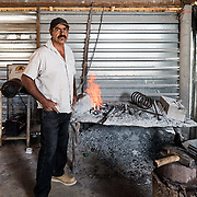 Hilario Higuera standing next to his forge.