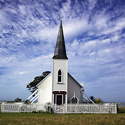 Raukokore's Anglican Church sits on the shore line of the small villiage of Raukokore, a small settlement close to the East Cape in the northeastern North Island of New Zealand. It is located on State Highway 35, close to the mouth of the Raukokore River, 40 kilometres to the west of Hicks Bay..The Anglican church is a landmark of the East Cape region, which stands isolated close to the shore of Papatea Bay.  North Island, New Zealand. 19th January 2010 Photo Tim Clayton.