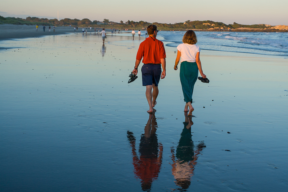 A couple walking on the town beach at sunset, Narragansett, Rhode Island.