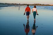 A couple walking on the town beach at sunset, Narragansett, Rhode Island.