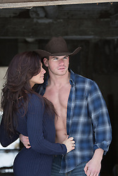 cowboy with an open shirt and a beautiful girl together on a ranch