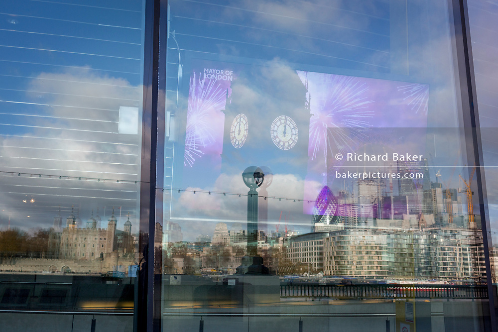 With the City skyline in the distance, a New Year's Eve fireworks display appears on a screen from inside City Hall on the Southbank, on 14th December 2017, in London, England.