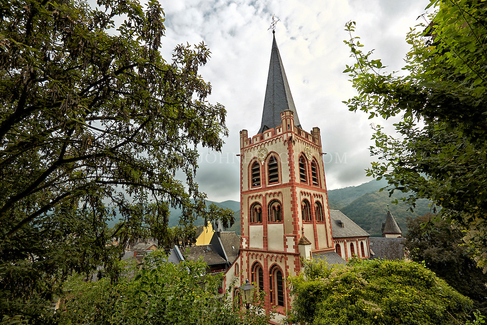 View of St Peter Church, and includes mountains and cloudy skies in the background, Bacharach, Germany.