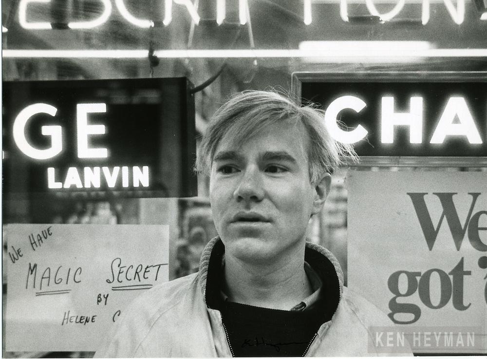 Warhol posing in a Broadway shop.