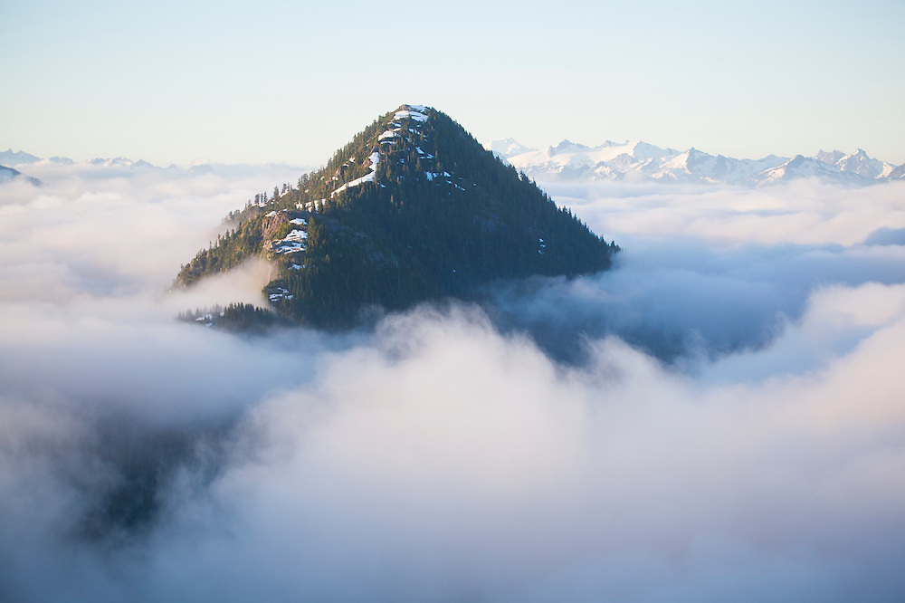 Oakes Peak rises above the low clouds filling Bacon Creek drainage, Mount Baker-Snoqualmie National Forest, Washington. Snowking Mountain, Mount Tommy Thompson, Mount Chaval and other mountains are visible in the distance.