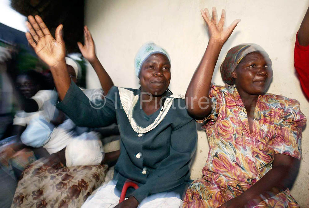 Women MDC supporters show their hands, the MDC symbol, during a gathering at Rukweza village, Manicaland to hear prospective MDC candidate Piesha speak to them.