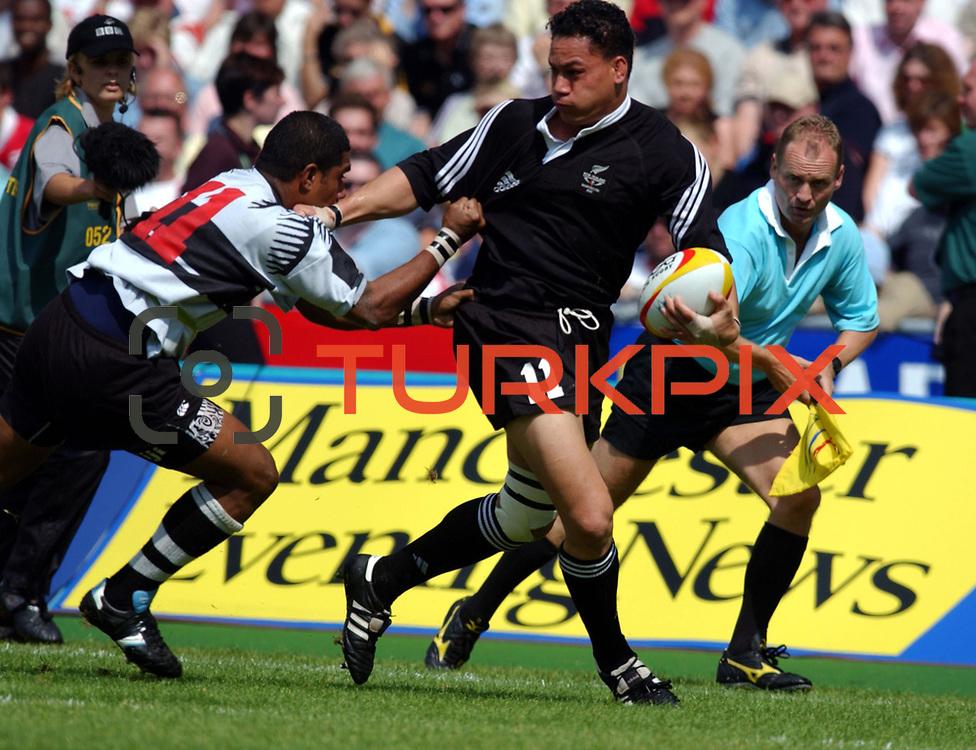 New Zealand's Chris Masoe is tackled by Fiji's  Saisi Fuli