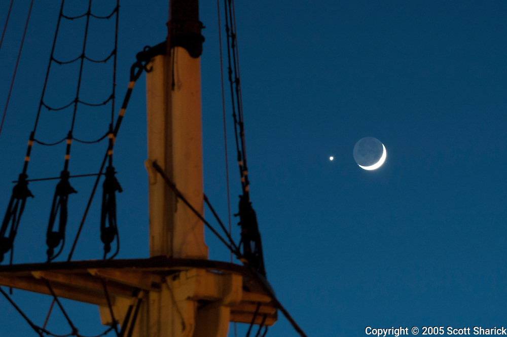 A crescent moon and Venus high in the sky with a wooden boat mast in the foreground.