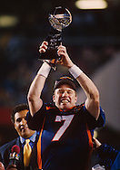 MIAMI, FL-FEBRUARY 1:  NFL Hall of Fame quarterback John Elway holds up the Super Bowl trophy after being named MVP of Super Bowl XXXIII against the Atlanta Falcons at Joe Robbie Stadium in Miami, Florida on February 1, 1999.  Elway played for the Denver Broncos from 1983-1999.  (Photo by Ron Vesely)