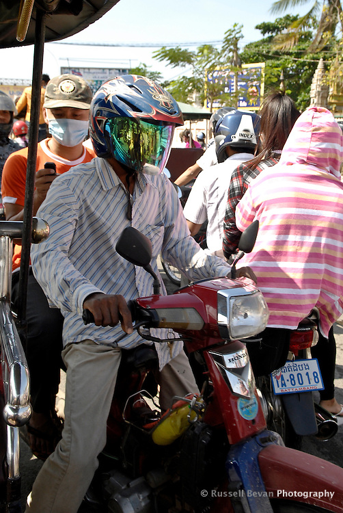 A moto driver works through traffic while his passenger sends a SMS