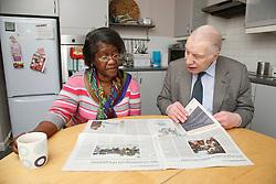 Carer and pensioner talking over newspaper.
