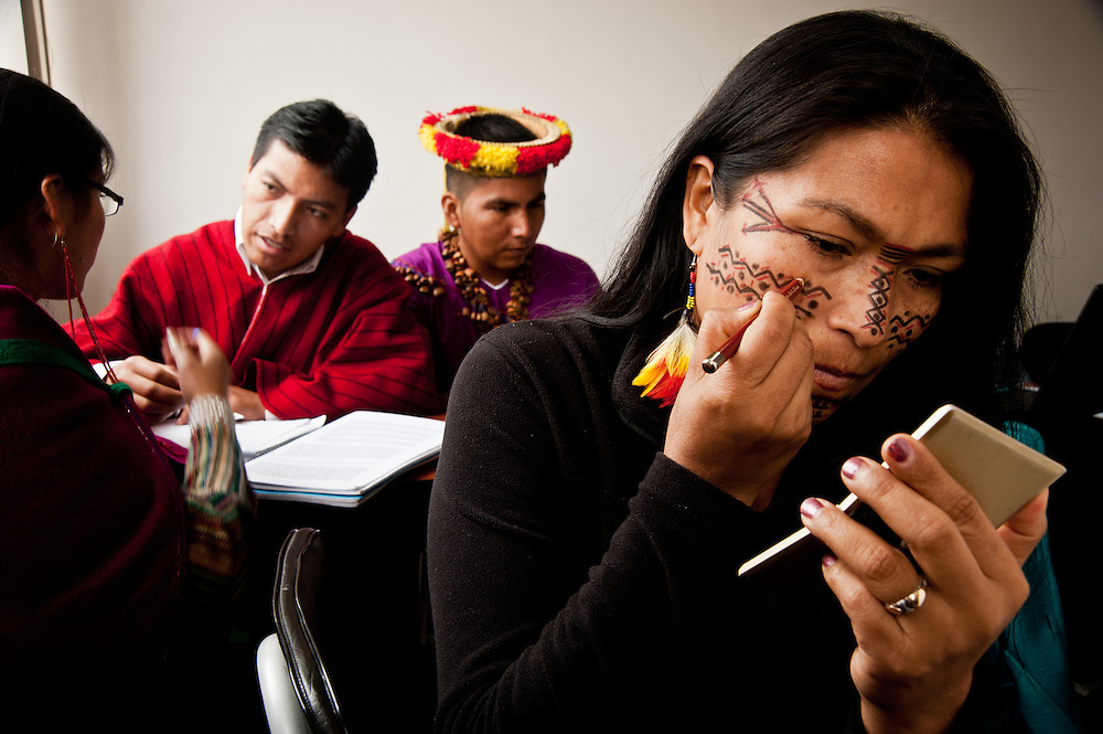 During a break in class, an indigenous Eduacorian student applies traditional make-up.