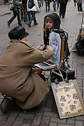 Moscow, Russia, 21/04/2004..The historic Stary Arbat [Old Arbat] and surrounding lanes are Moscow's main pedestrian precinct, and an attraction for Muscovites and tourists alike. One of the area's many street artists at work drawing a portrait.