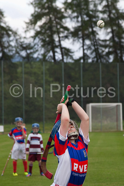Under 12 school teams boys and girls play the traditional game of Shinty. Kingussie (in red and blue) versus Banavie school from Fort William. Many of the players are sons or daughters of first team players.<br /> A player does a 'shy'.<br /> <br /> Shinty, or 'Camanachd' in Scottish, is a game only played mostly in the Highlands between teams representing villages and towns. The game is older than the recorded history of Scotland and is played on a grass pitch using a small ball and sticks (called a caman). Each team consists of twelve players and the game is played over two halves of 45 minutes. The the aim is to score goals only by using the caman. A ball hit over the sideline results in a 'shy'. To do a shy a player must throw the ball above his or her head and hit the ball with the caman directly over the head using both hands.