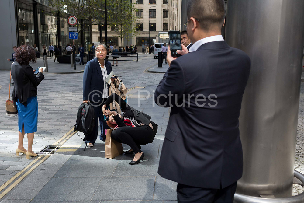 An Asian business lady visitor comically contorts her body in order to take a photo of a colleague against London skyscrapers in the City of London, aka The Square Mile the capitals financial district, on 2nd September 2019, in London, England.