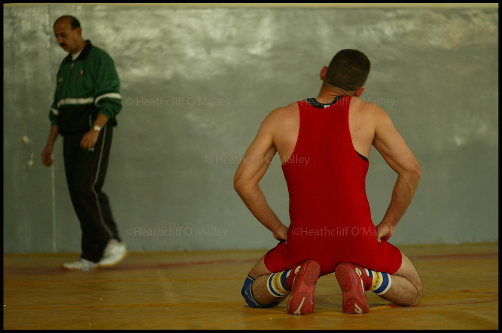The Iraqi Olympic Wrestling Team train at the delapidated Aadamiyah Sports centre in Baghdad.Once brutalised by Saddam's son Uday Hussein who was previously head of the Olympic Committee in Iraq, the wrestlers now dream of a new life in the lucrative world of international sport...Pic shows Hassan Fardel,28,a freestyle wrestler who was tortured by Uday's Fedayeen,limbering up before a training session.