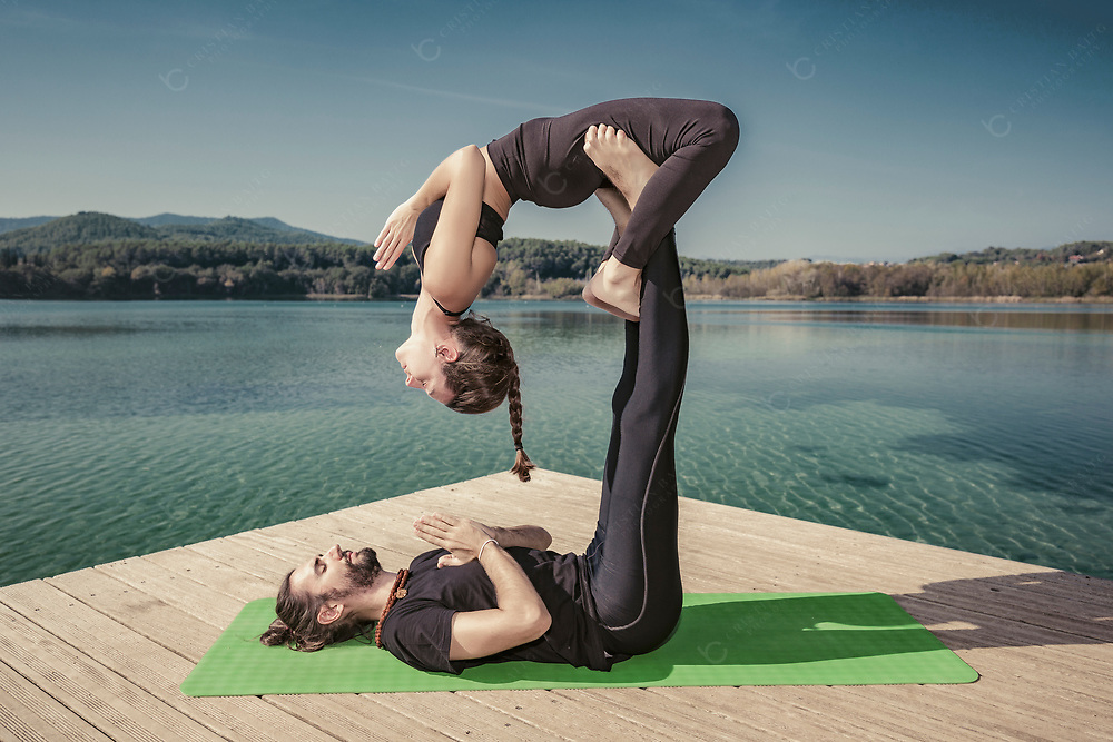 Man and woman doing acroyoga Reverse Throne Cascade pose