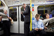 London Underground passengers on a Circle Line tube train reading free newspapers.
