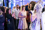 """Hair sculpture models pose for photographs wit the crowd during """"Hair Affair: The Art of Hair"""" at Madison Museum of Contemporary Art in Madison, WI on Thursday, April 25, 2019. The sixth biennial brought an array of designers and stylists from across Wisconsin to create under the theme of """"Zodiac."""""""