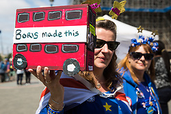 London, UK. 26 June, 2019. A model of a 'Boris Made This' red bus at the 50th birthday celebration for noted anti-Brexit campaigner Steve Bray of SODEM (Stand of Defiance European Movement) outside Parliament. Yesterday, Conservative leadership candidate Boris Johnson stated during an interview on Talk Radio that he relaxes by crafting and painting model buses made from wooden crates.