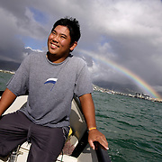 HONOLULU, HAWAII, November 8, 2007: Tadd Fujikawa, a sixteen-year-old professional golfer, makes his way to shore with his father after a little fishing in Honolulu, Hawaii.
