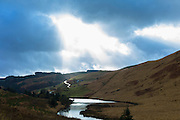 Sunlight through cloud shining on river and empty road along a valley in the Brecon Beacons mountain range in Wales, UK