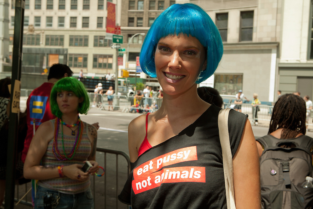 """Young woman with a message, waiting for the start of the 2011 Pride Parade, New York. She wears a tee shirt reading """"eat pussy not animals."""""""