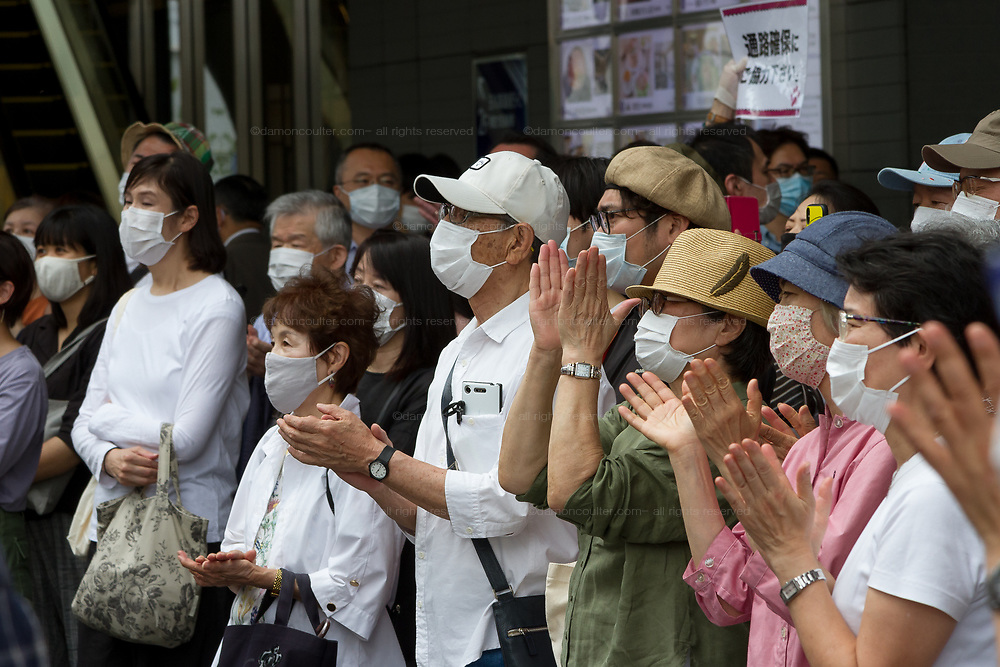 Japanese people. wearing facemarks against COVID-19, applaud Taro Yamamoto, a former actor and politician, campaigns for election as the Tokyo Governor in Futaka Tamagawa, Tokyo, Japan. Tuesday June 23rd 2020. The incumbent  governor, Yuriko Koike (not pictured) is expected to be reelected when the election are held on Sunday July 5th 2020