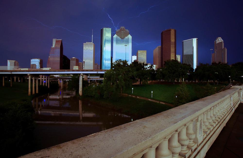 Lightning in night sky over Houston, Texas skyline with Sabine Bridge and Buffalo Bayou in foreground.
