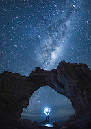 The Milky Way and a meteor shower above the Wolfberg Arch in the Cederberg Mountains, South Africa.