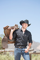 All American cowboy with a saddle on a ranch