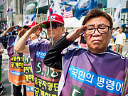 09 JUNE 2018 - SEOUL, SOUTH KOREA: Men salute while the South Korean national anthem is played during a pro-American rally in downtown Seoul. Participants said they wanted to thank the US for supporting South Korea and they hope the US will continue to support South Korea. Many were also opposed to ongoing negotiations with North Korea because they don't think Kim Jong-un can be trusted to denuclearize or to not attack South Korea.     PHOTO BY JACK KURTZ
